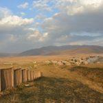 ...mit Blick über Feldern, Berge und ein Dorf